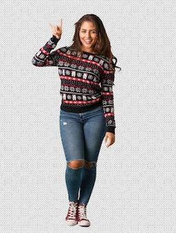 Corps complet jeune femme portant un maillot de noël faisant un geste rock
