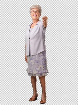 Corps plein femme senior gaie et souriante pointant vers l'avant