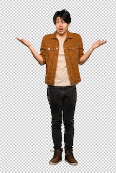 Un coup complet d'un homme asiatique avec une veste brune avec une expression faciale choquée