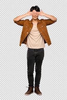 Un coup complet d'un homme asiatique avec une veste marron couvrant les yeux par les mains