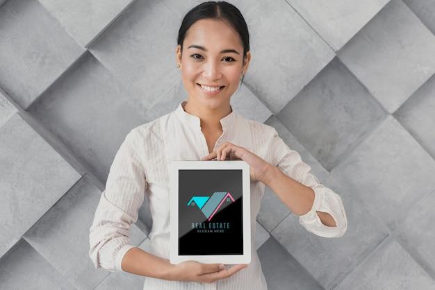 Coup moyen de femme d'affaires tenant une tablette avec de l'immobilier