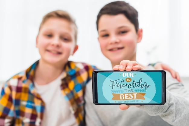 Coup moyen garçons heureux avec smartphone