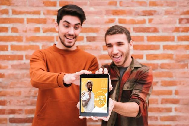 Coup moyen mecs heureux tenant une tablette