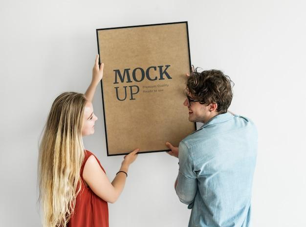 Couple accrochant un cadre