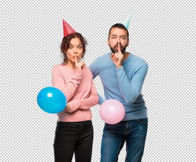 Couple, à, ballons, et, anniversaire, chapeaux, montrer, a, geste silence, mettre doigt, dans, bouche