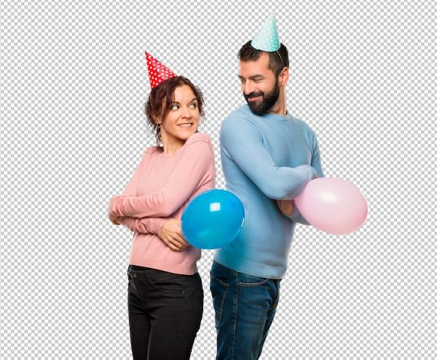 Couple, à, ballons, et, anniversaire, chapeaux, regarder par-dessus l'épaule, sourire