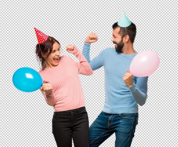 Couple avec des ballons et des chapeaux d'anniversaire célébrant une victoire en position gagnante