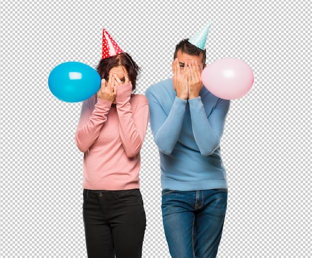 Couple avec des ballons et des chapeaux d'anniversaire couvrant les yeux avec les mains et regardant à travers les doigts