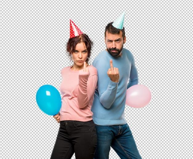 Couple avec des ballons et des chapeaux d'anniversaire faisant un geste de corne. expression négative