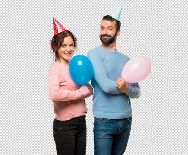 Couple avec des ballons et des chapeaux d'anniversaire gardant les bras croisés en position latérale en souriant