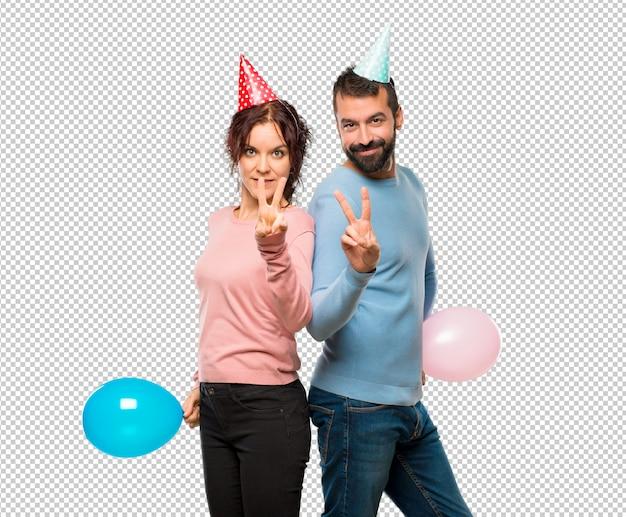 Couple avec des ballons et des chapeaux d'anniversaire heureux et en comptant deux avec les doigts