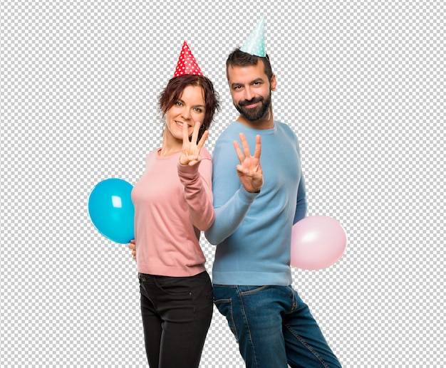 Couple avec des ballons et des chapeaux d'anniversaire heureux et en comptant trois avec les doigts