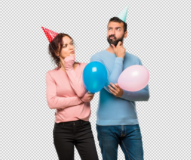 Couple avec des ballons et des chapeaux d'anniversaire en pensant à une idée