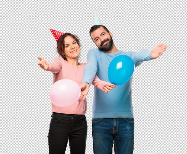 Couple avec des ballons et des chapeaux d'anniversaire présentant et invitant à venir. heureux que tu sois venu