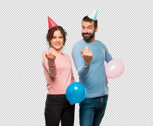 Couple avec des ballons et des chapeaux d'anniversaire présentant et invitant à venir avec la main