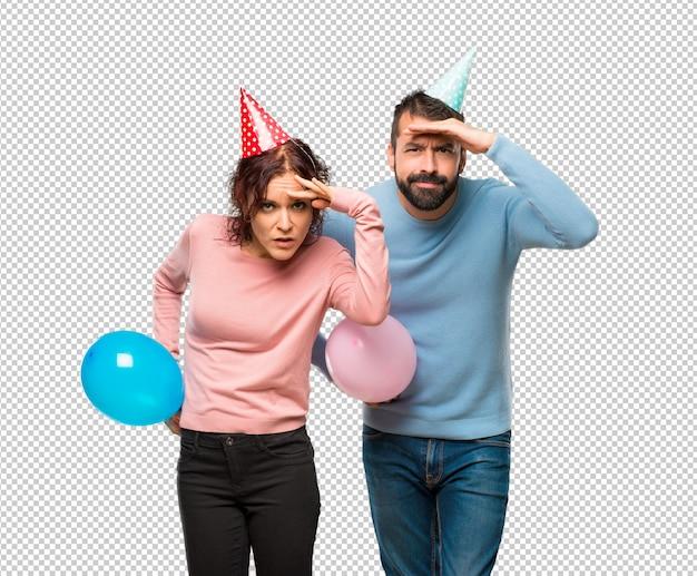 Couple avec des ballons et des chapeaux d'anniversaire regardant loin avec la main pour regarder quelque chose