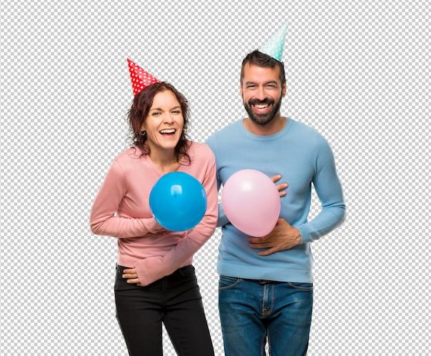 Couple avec des ballons et des chapeaux d'anniversaire en souriant beaucoup tout en mettant les mains sur la poitrine