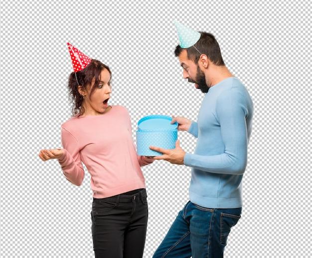 Couple avec des chapeaux d'anniversaire et des cadeaux