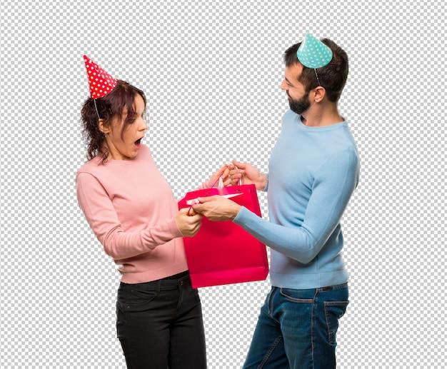 Couple avec des chapeaux d'anniversaire et des sacs à provisions