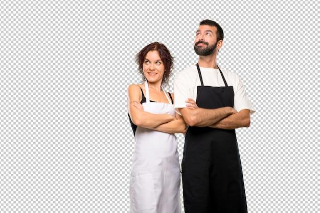Couple de cuisiniers levant les yeux en souriant