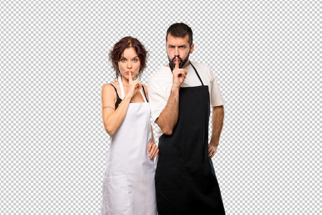 Couple de cuisiniers montrant un geste de silence mettant un doigt dans la bouche