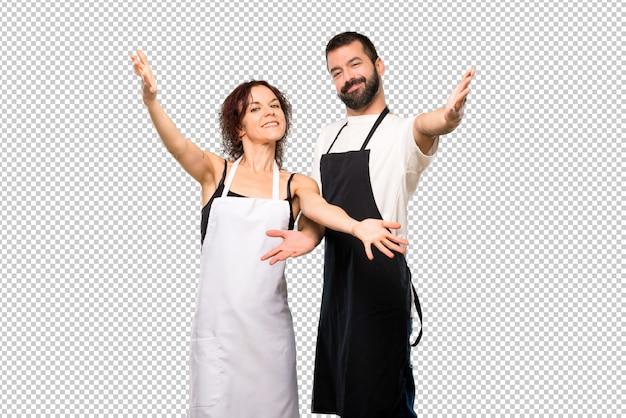 Couple de cuisiniers présentant et invitant à venir. heureux que tu sois venu