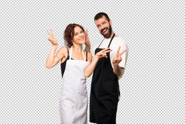 Couple de cuisiniers souriant et montrant des signes de victoire à deux mains