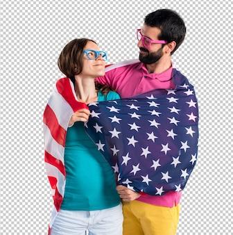 Couple dans des vêtements colorés tenant un drapeau américain