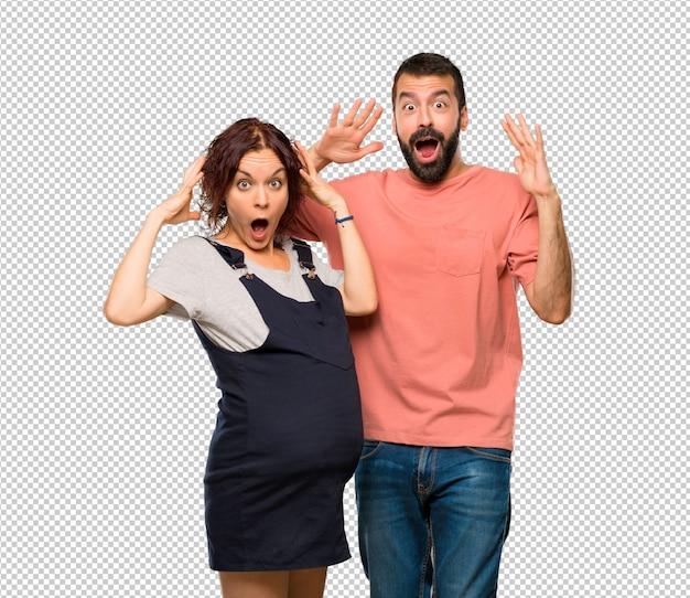 Couple avec une femme enceinte avec une expression faciale surprise et choquée
