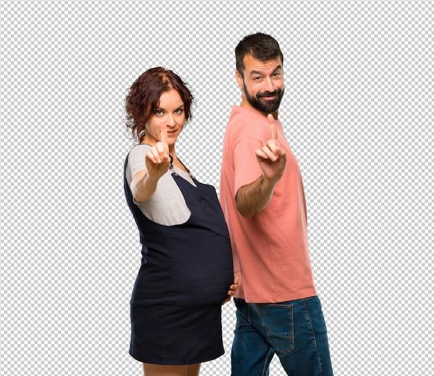 Couple avec femme enceinte montrant et en levant un doigt en signe du meilleur