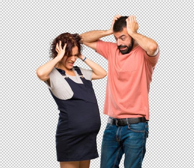 Couple avec femme enceinte prend les mains sur la tête car a la migraine