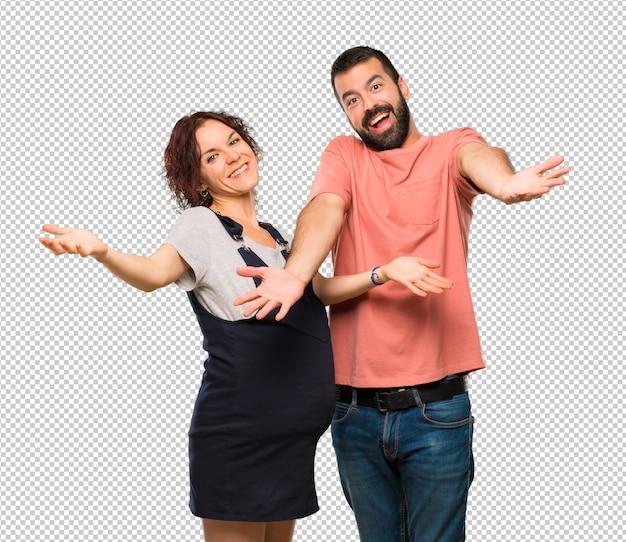 Couple avec femme enceinte présentant et invitant à venir. heureux que tu sois venu