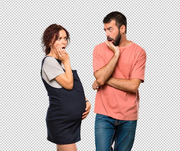 Couple avec une femme enceinte surprise et choquée en regardant à droite