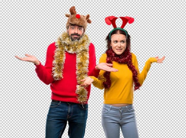 Couple habillé pour les vacances de noël ayant des doutes et avec une expression de visage confuse