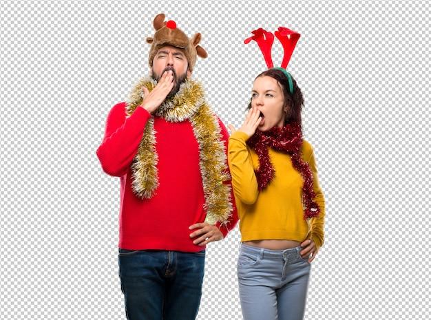 Couple habillé pour les vacances de noël bâillant et se couvrant la bouche avec la main. expression endormie