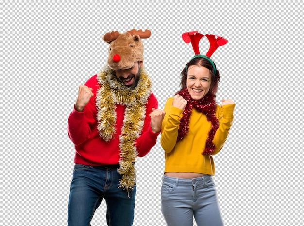 Couple habillé pour les vacances de noël célébrant une victoire et heureux d'avoir
