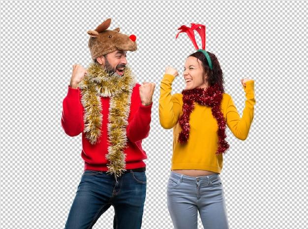 Couple habillé pour les vacances de noël célébrant une victoire en position de gagnant