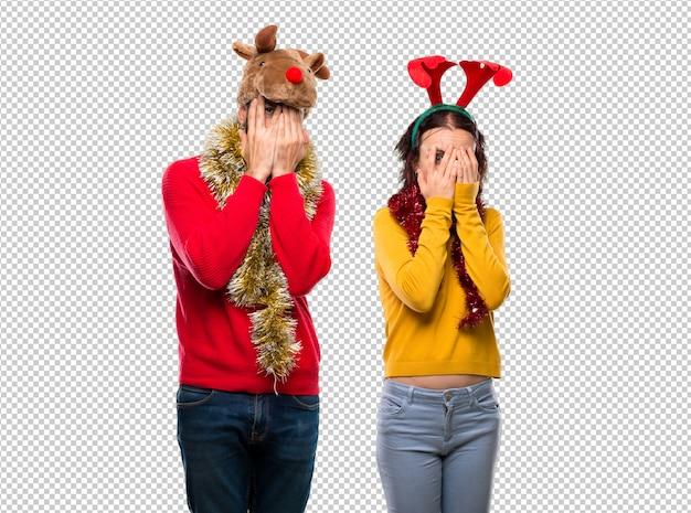 Couple habillé pour les vacances de noël couvrant les yeux avec les mains et regardant à travers les doigts