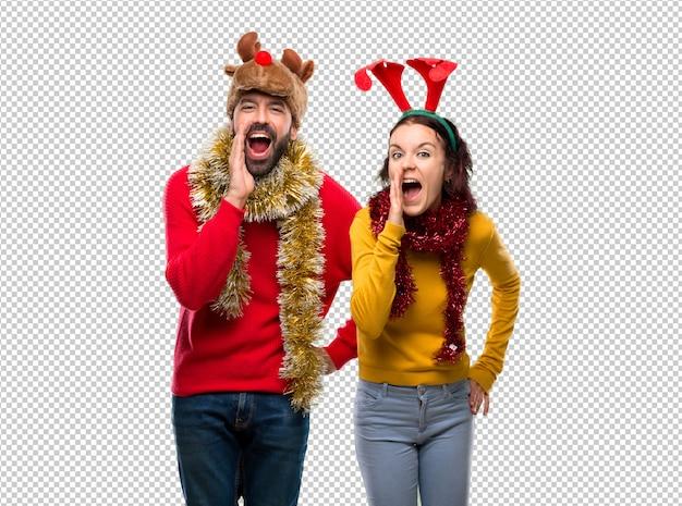 Couple habillé pour les vacances de noël criant sur le côté et annonçant quelque chose
