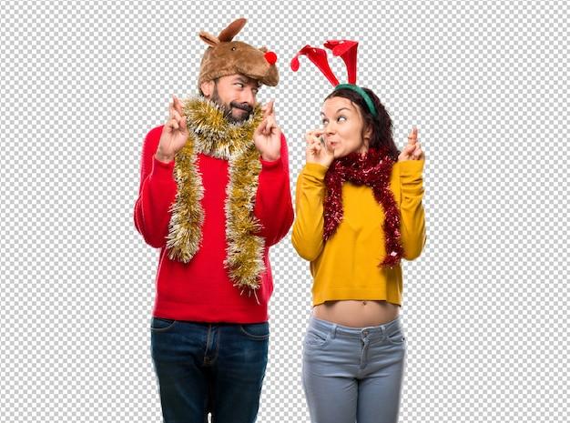 Couple habillé pour les vacances de noël avec les doigts croisés et souhaitant le meilleur