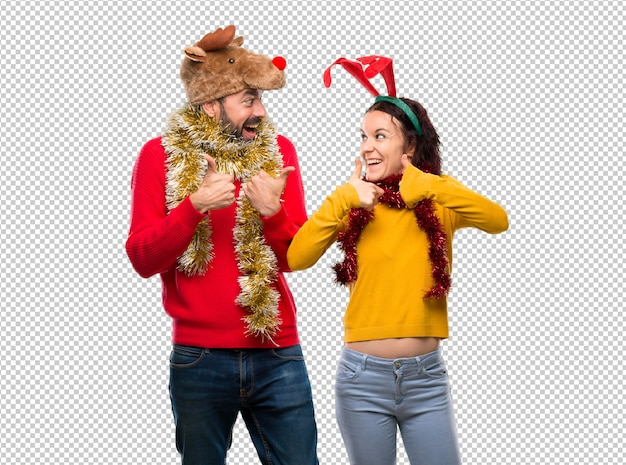 Couple habillé pour les vacances de noël donnant un geste du pouce levé et souriant