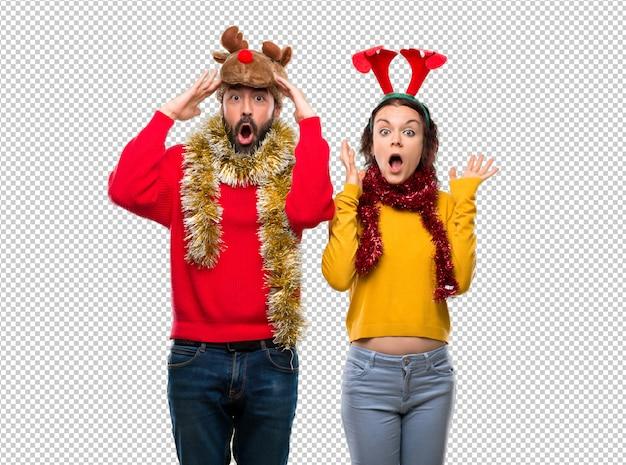 Couple habillé pour les vacances de noël avec une expression faciale surprise et choquée