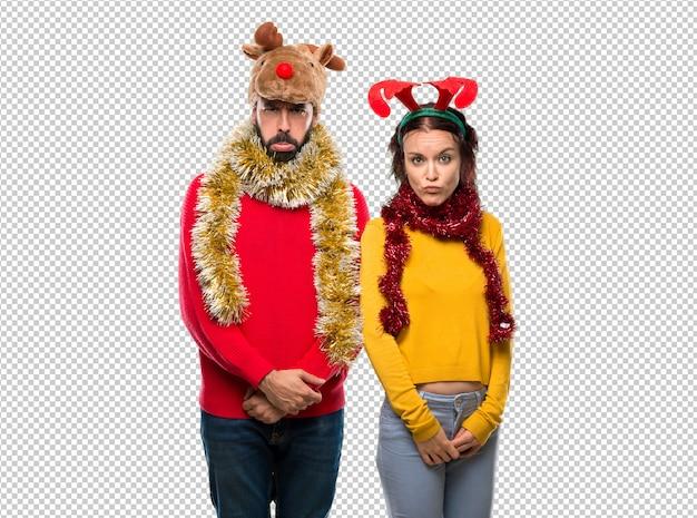 Couple habillé pour les vacances de noël avec une expression triste et déprimée. geste sérieux