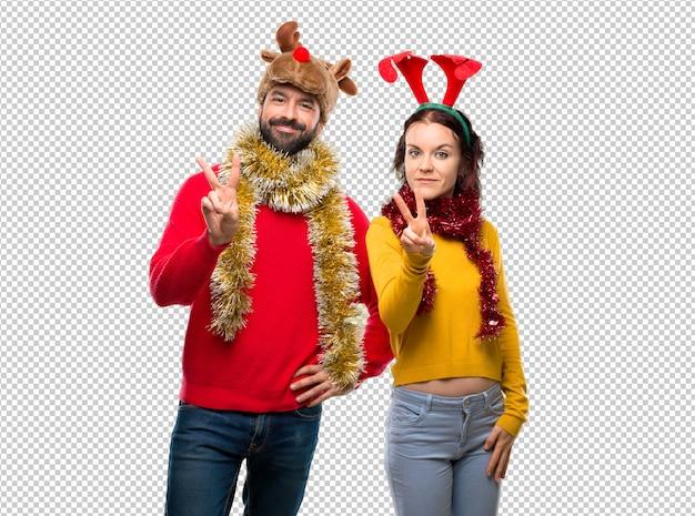 Couple habillé pour les vacances de noël heureux et comptant avec deux doigts
