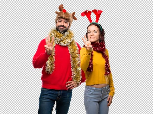 Couple habillé pour les vacances de noël heureux et comptant trois avec les doigts