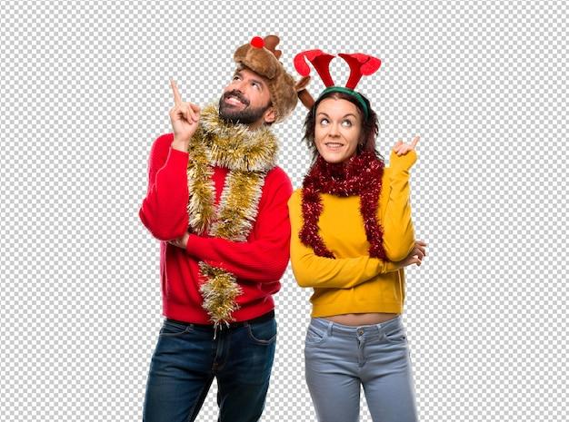 Couple habillé pour les vacances de noël montrant du doigt une bonne idée et levant les yeux