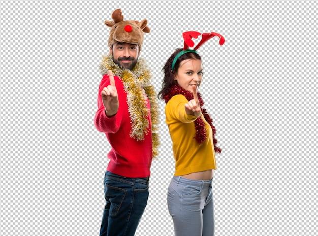 Couple habillé pour les vacances de noël montrant et en levant un doigt en signe du meilleur