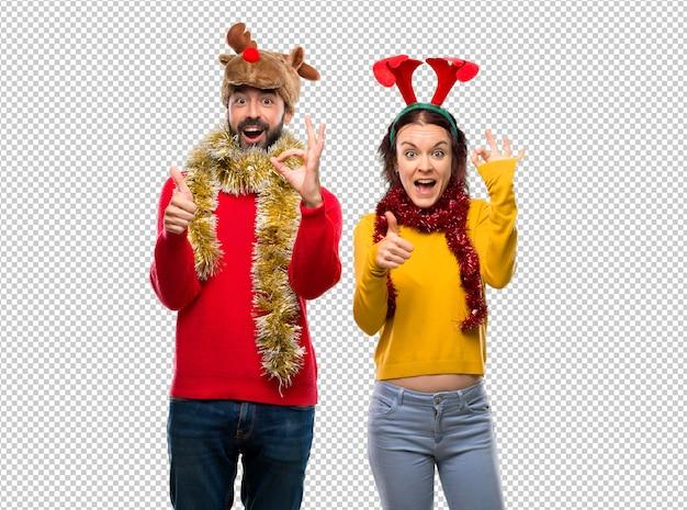 Couple habillé pour les vacances de noël, montrant le signe ok et donnant un geste du pouce