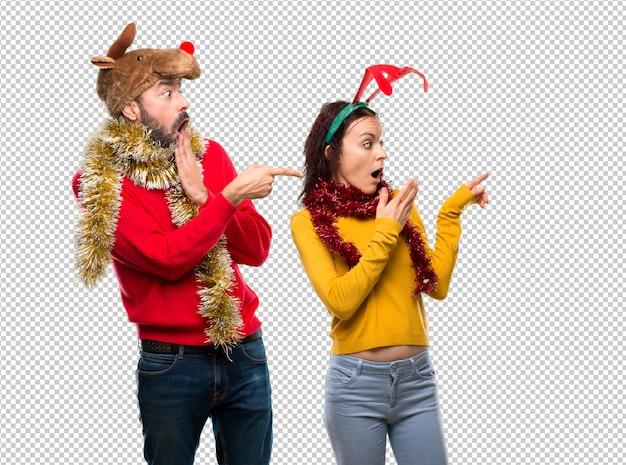 Couple habillé pour les vacances de noël, pointant le doigt vers le côté et présentant un