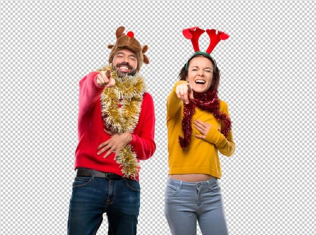 Couple habillé pour les vacances de noël pointant du doigt quelqu'un et riant beaucoup